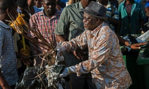 President John Magufuli cleans outside the State House in Dar es Salaam in December.