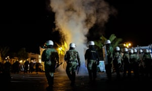 Riot police try to keep local protesters away from migrants during clashes in Mytilene.