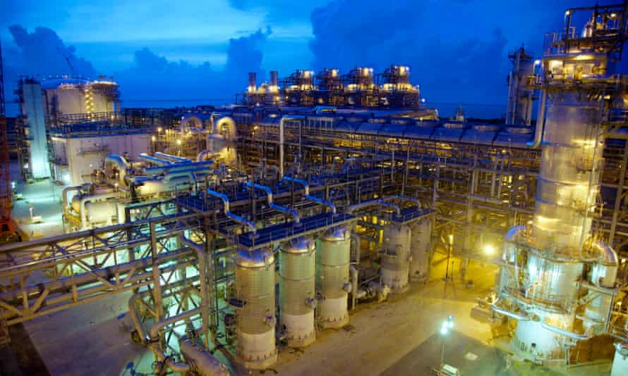 brightly lit gas plant against a blue sky