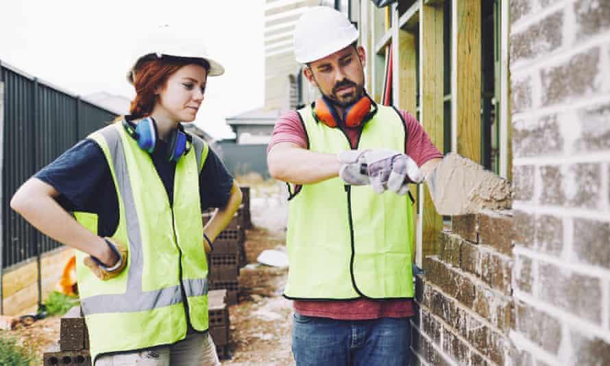 man teaching woman to build brick wall