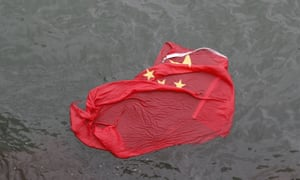 A Chinese flag floats on the surface after it was thrown in the water by protesters