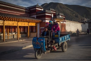 A man drives a vehicle with women standing on it, near the Labrang Monastery in Xiahe, an ethnically-Tibetan town in Gansu province, China