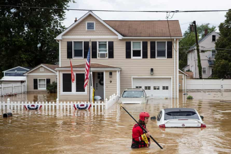 A rescue crew member wades through high waters following a flash flood, as Tropical Storm Henri makes landfall, in Helmetta, New Jersey, on Sunday.