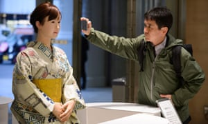 A customer takes a photograph of Toshida's humanoid robot Aiko Chihira
