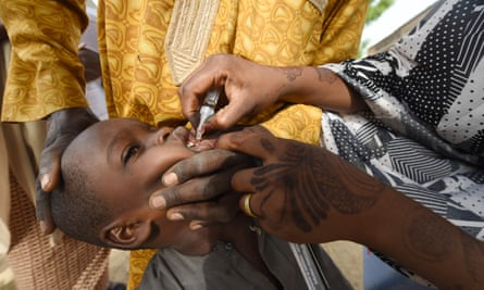A health worker administers a polio vaccine to a child in north-west Nigeria. 'The global project has involved 20 million volunteers vaccinating nearly 3 billion children.'