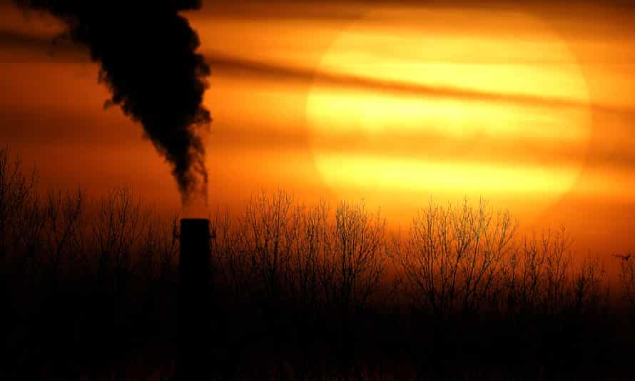 A smokestack from a Evergy's Hawthorn coal-fired power plant is silhouetted against the setting sun in Kansas City, USA