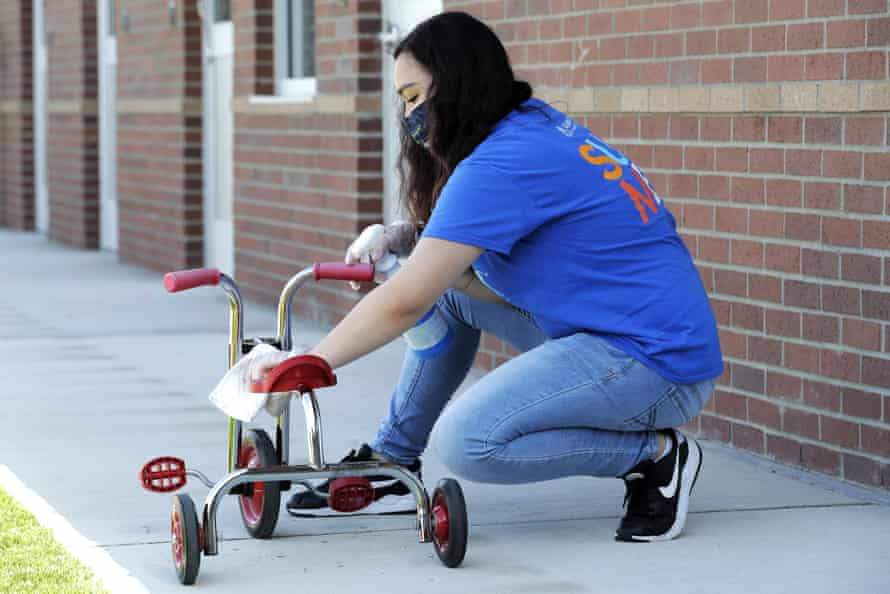 Alena Kleinman cleans a tricycle at Frederickson KinderCare in Tacoma, Washington.