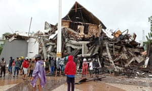 People look at the damaged office of governor of West Sulawesi following an earthquake in Mamuju