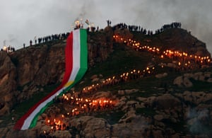 Akra, IraqIraqi Kurds holding lit torches walk up a mountain, draped in a large Kurdish flag as they celebrate the Noruz spring festival. The Persian New Year is an ancient Zoroastrian tradition celebrated by Iranians and Kurds which coincides with the vernal (spring) equinox and is calculated by the solar calender