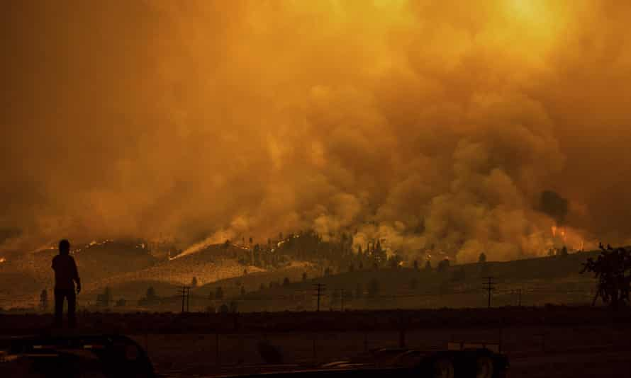 A truck driver who hauls fire equipment watches as the Sugar fire, part of the Beckwourth Complex fire, burns in Doyle, California, on Saturday. Smoke rises in the background