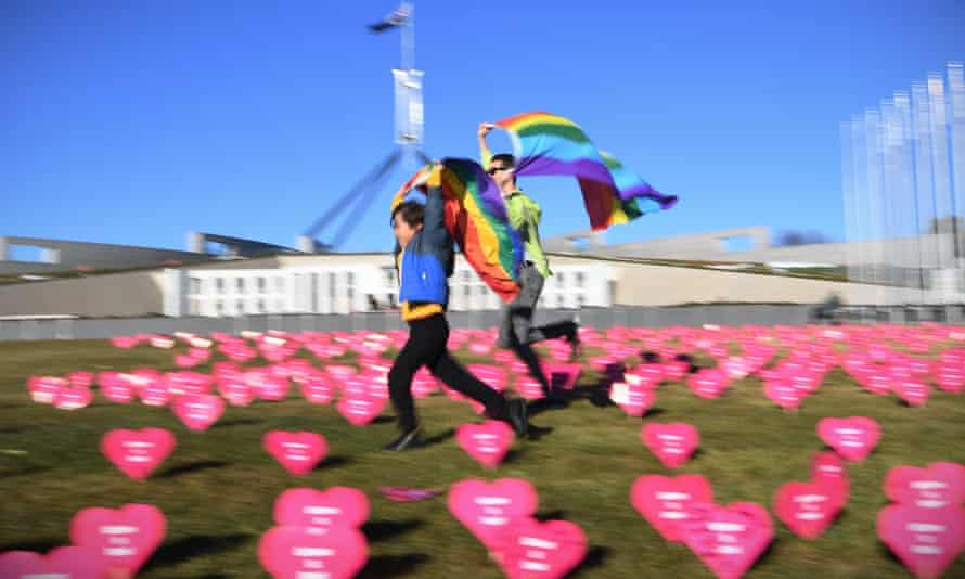 Marriage equality advocate Russell Nankervis (right) and a child run through the 'Sea of Hearts' event supporting Marriage Equality outside Parliament House in Canberra, 8 August  2017.