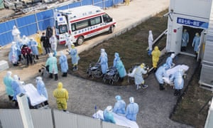 Medical workers in protective suits help transfer the first group of patients into the newly-completed Huoshenshan temporary field hospital