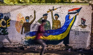 a Sudanese protester runs past a recently painted mural