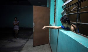 A mental health patient leans out of her room at the Caracas Psychiatric Hospital, Venezuela