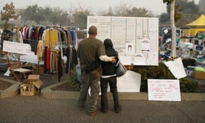 Tera Hickerson, right, and Columbus Holt embrace as they look at a board with information for services at a makeshift encampment outside a Walmart for people displaced by the Camp fire.