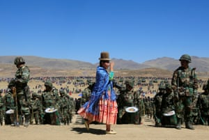 Achacachi, Bolivia Salute! A traditionally dressed photographer takes part in a parade to commemorate the founding of the national armed forces in Kjasina