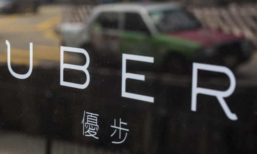 """A taxi is reflected in a window at the office of taxi-hailing service Uber Inc in Hong Kong, China August 12, 2015. Police raided the Hong Kong offices of taxi-hailing service Uber Inc on Tuesday and arrested five drivers for the """"illegal use of vehicles for hire"""", police said. REUTERS/Tyrone Siu"""