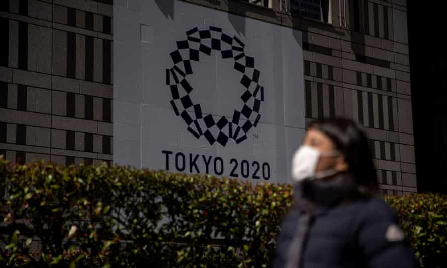 A woman wearing a protective face mask, following an outbreak of the coronavirus, walks past a banner for the upcoming Tokyo 2020 Olympics in Tokyo