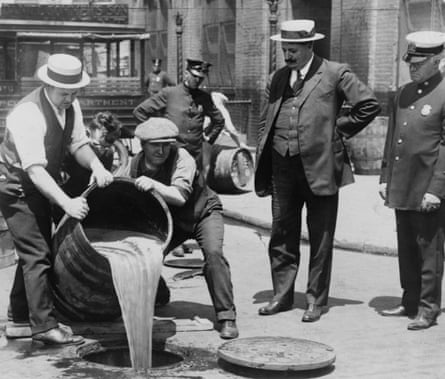 A barrel of confiscated illegal beer being poured down a drain.
