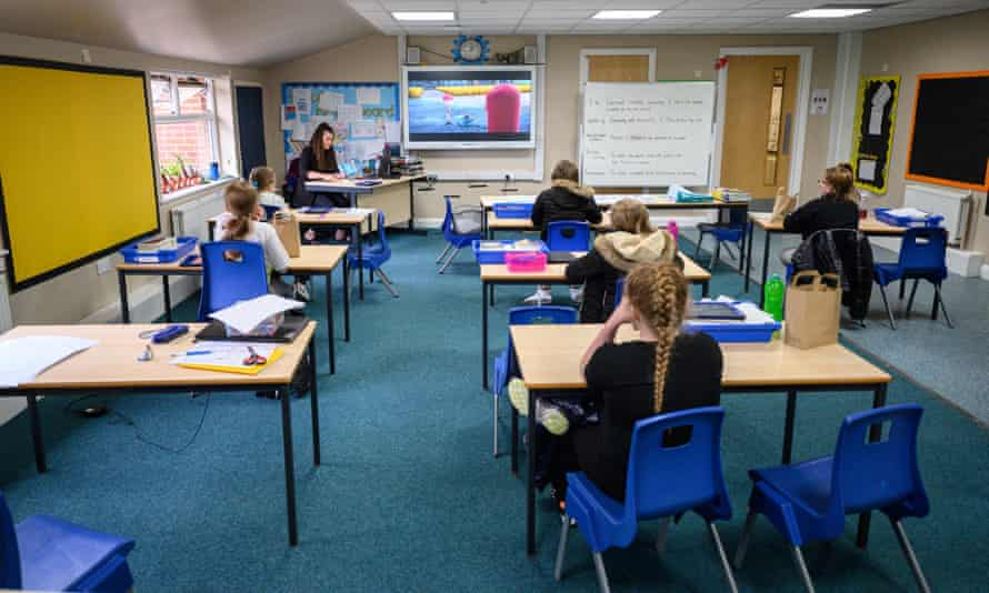 Key Stage 2 pupils eat their lunches individually at their desks, sitting well apart from each other, at Willowpark Primary Academy in Oldham, north-west England
