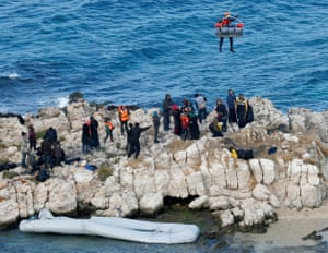 A Turkish coastguard crew member hangs on a rope attached to a helicopter above some rocks near İzmir.