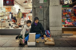 Miriam and her son in street with notice written on cardboard