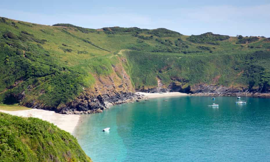 Beaches at Lantic Bay with blue sea and green cliffs behind