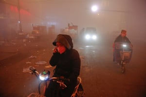 People make their way through heavy smog in Shengfang.