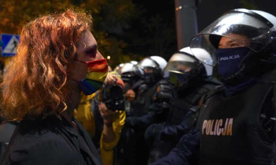 A protester confronts police in Warsaw