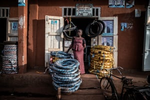 A vendor selling motorcycle tyres waits by the roadside at a market in Butembo