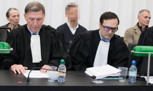 The three defendants sit behind lawyers during their trial in Ghent.