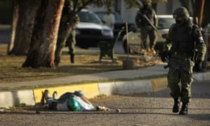 A member of the military police walks by a body with a mask in the street, one of numerous murders over a 24-hour period, on 26 March 2010 in Ciudad Juárez, Mexico, which has been racked by violent drug-related crime.