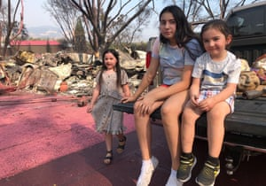The Guterrez children wait as their father, Artemio Guterrez, salvages a few items from their scorched mobile home in Talent, Oregon