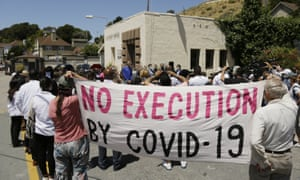 People hold up a banner at a news conference outside San Quentin state prison, 9 July 2020.