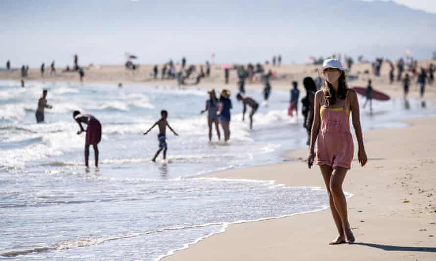 A woman wearing a face mask walks at Venice Beach during a heatwave amid the coronavirus pandemic, in Los Angeles, California, USA, 11 July 2020