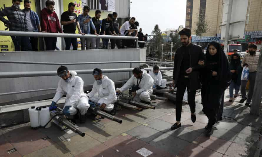 Firefighters prepare to disinfect a street in Tehran