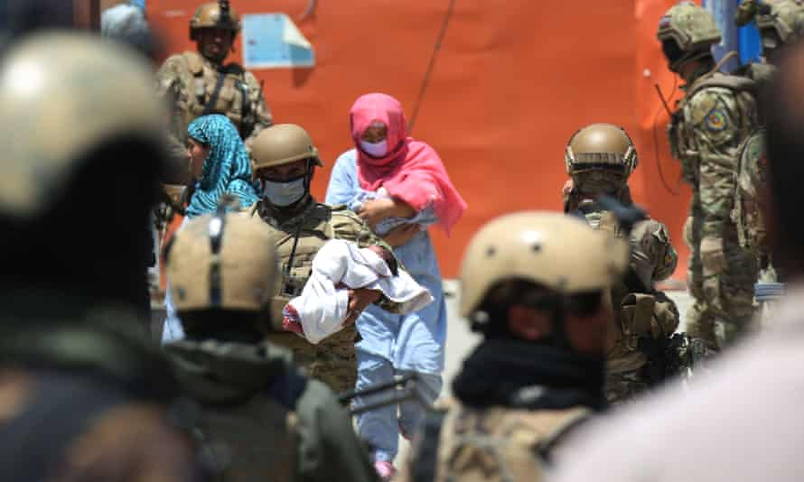 A security forces member and health worker carry babies from the site of the attack on the maternity wing of a Kabul hospital on 12 May.