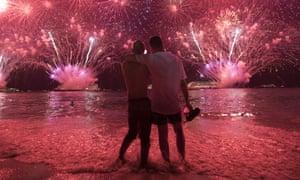 Two men watch the fireworks exploding over Copacabana Beach in Rio de Janeiro, Brazil.