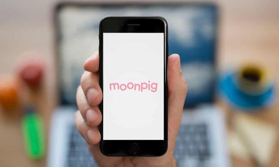 شخصی تلفن را در دست دارد که روی آن آرم صورتی Moonpig دیده می شود