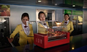 Hostesses prepare hot dogs at a floating restaurant in Pyongyang .
