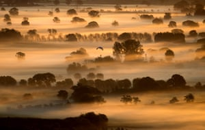 Mist lingers as the sun rises over the Somerset Levels on the autumn equinox