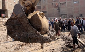 Egyptian workers lift parts of statue