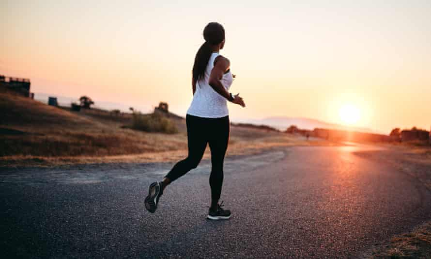 woman Running On Road At Sunset