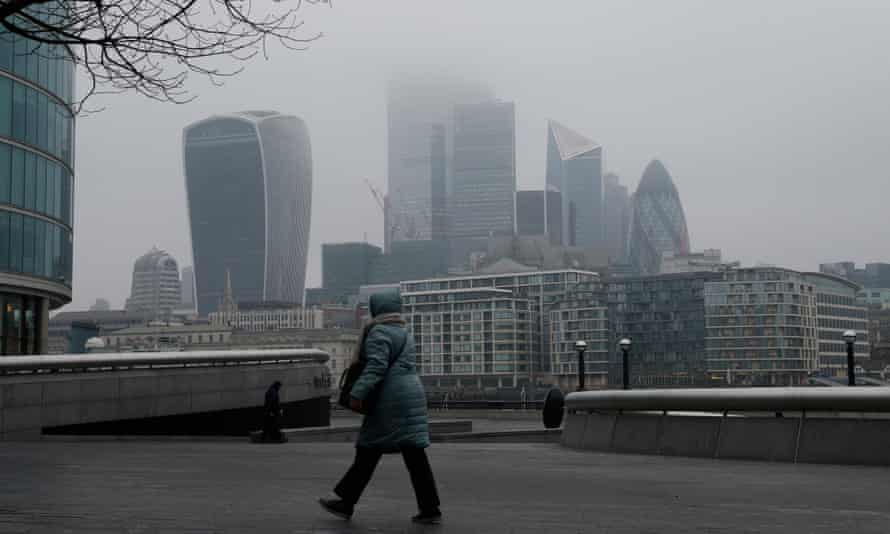 A woman walks past a view of the City of London skyline at sunrise in March