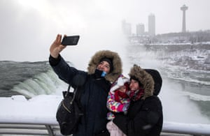 Niagara falls, NYA young family take selfies in front of the freezing falls as sub-zero temperatures are expected across Canada and the United States.