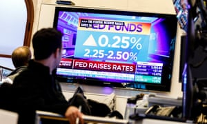Traders watch news reports about the United States Federal Reserve's decision to raise interest rates today
