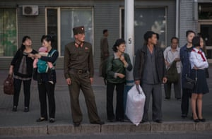 Commuters wait for a bus during the morning rush hour in Pyongyang, North Korea