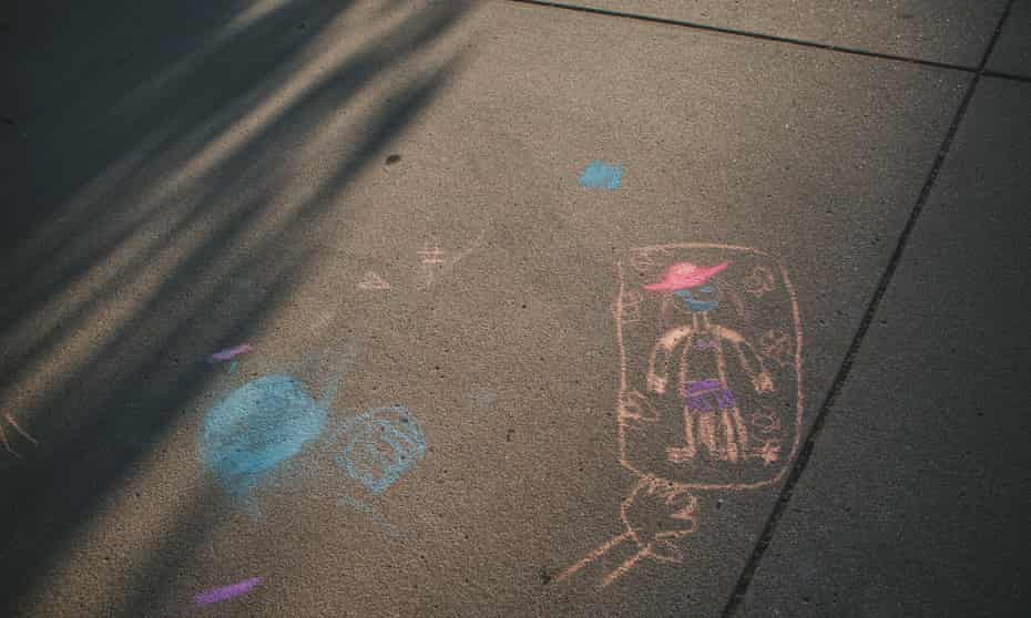 Evening sunlight shines on a child's pavement chalk drawing.