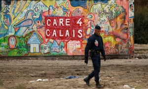 A riot policeman patrols close to where 1,500 minors are being housed in converted shipping containers in Calais.