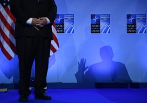 US Secretary of State Mike Pompeo looks on as President Trump casts a shadow during a press conference on the second day of the NATO summit